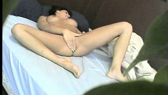 Lively dark along with stunning naturally-occuring tits entertaining her pussy on her sleep