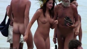 Voyeur girl bare on masses seashore